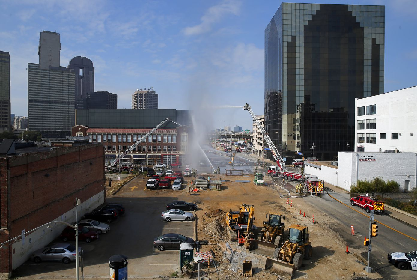 Dallas firefighters battle a fire caused by a ruptured gas line at a construction site along Cesar Chavez Blvd at Main St. in downtown Dallas, Friday, March 10, 2017.