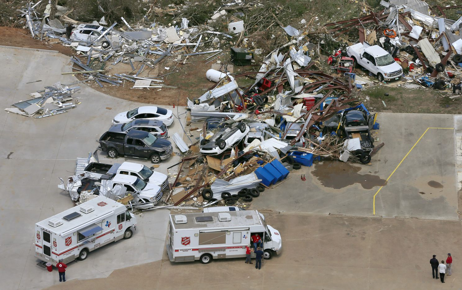 Two Salvation Army trucks are parked to help people in the parking lot of Interstate 20 Chrysler Dodge Jeep Ram of Canton where cars and trucks are thrown on top of each other in Canton, Texas, Sunday, April 30, 2017.