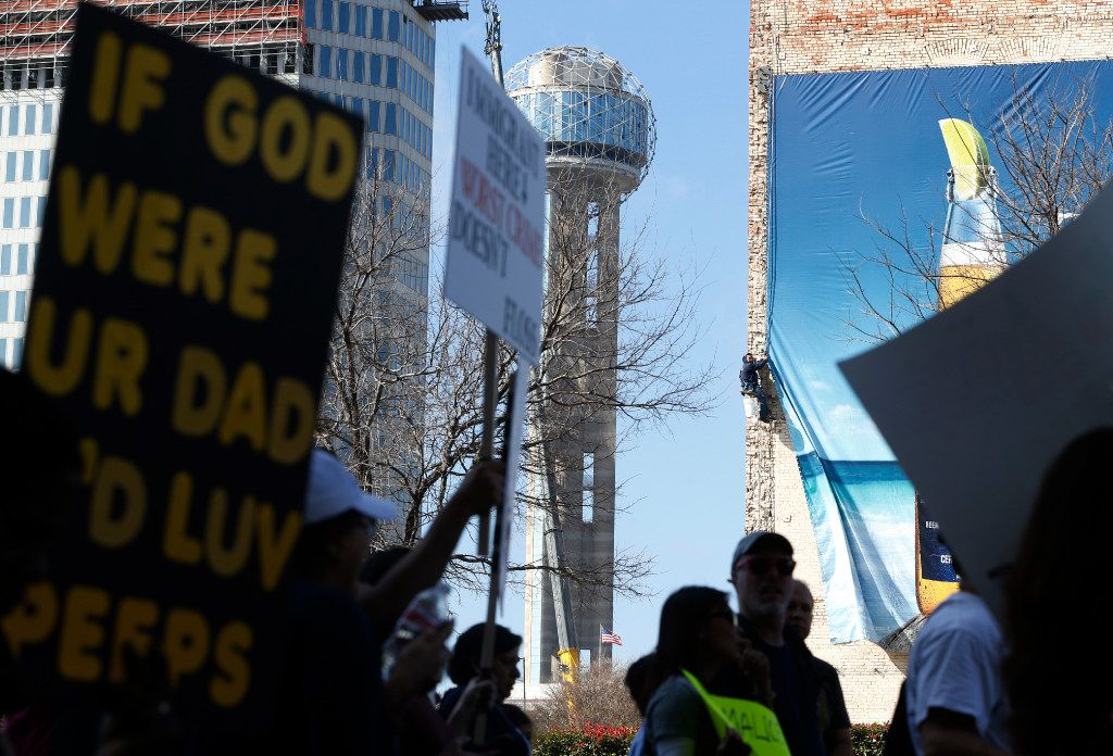 A worker watches the protest for immigrant and refugee communities as he removes a advertisement in downtown Dallas on February 18, 2017.  (Nathan Hunsinger/The Dallas Morning News)