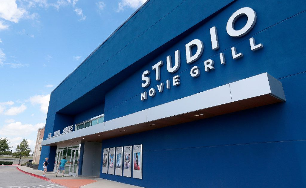 People walk into the Studio Movie Grill in The Colony. The Studio Movie Grill offers a cinema-dining experience to the customers who can order meals at their seats inside 11 auditoriums. (Jae S. Lee/Staff Photographer)