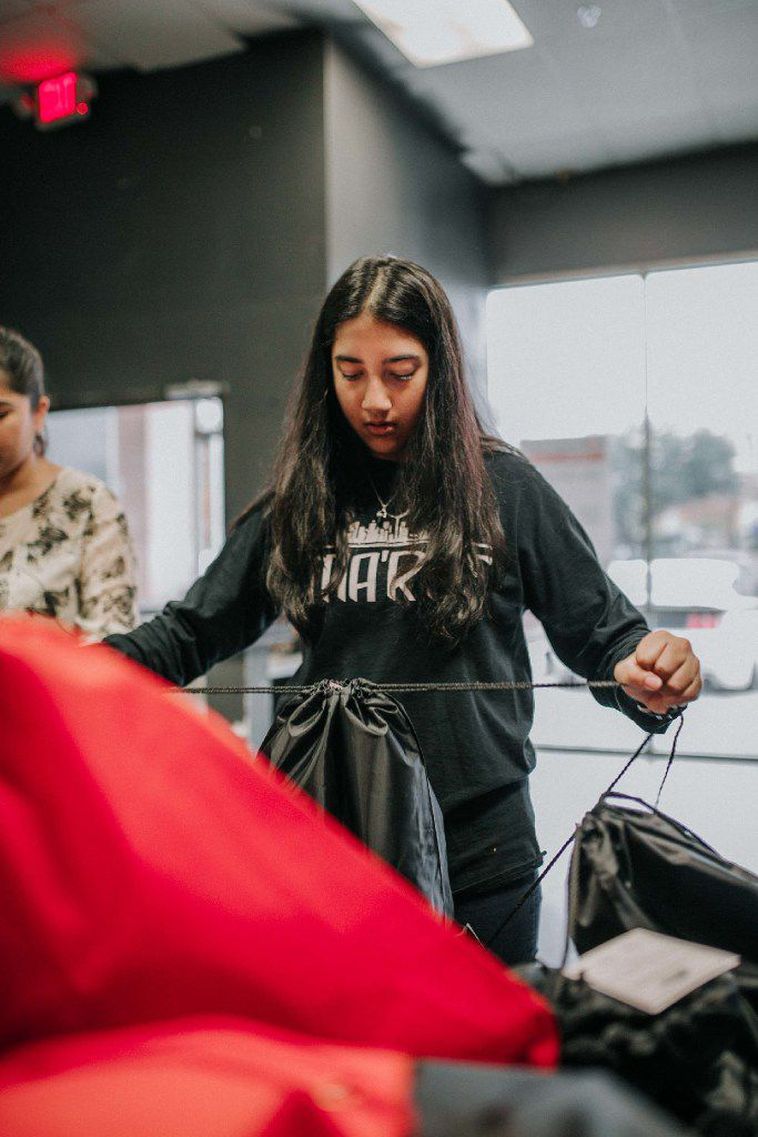 Saher Sayed, 15 packs a survival kit for the homeless in Dallas on an overcast Saturday. The packets include bottled water, socks, deodorant, toothpaste, a toothbrush, a washcloth and a blanket.