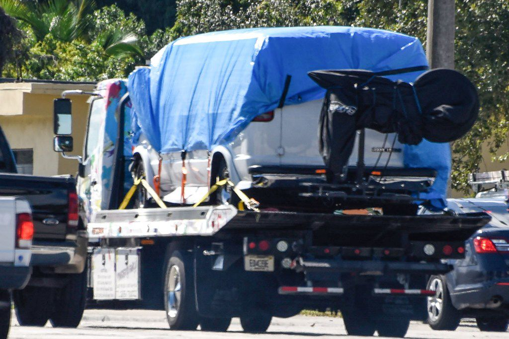 A van covered in blue tarp is towed by FBI investigators in Plantation, Fla., in connection with the 12 pipe bombs and suspicious packages mailed to top Democrats.