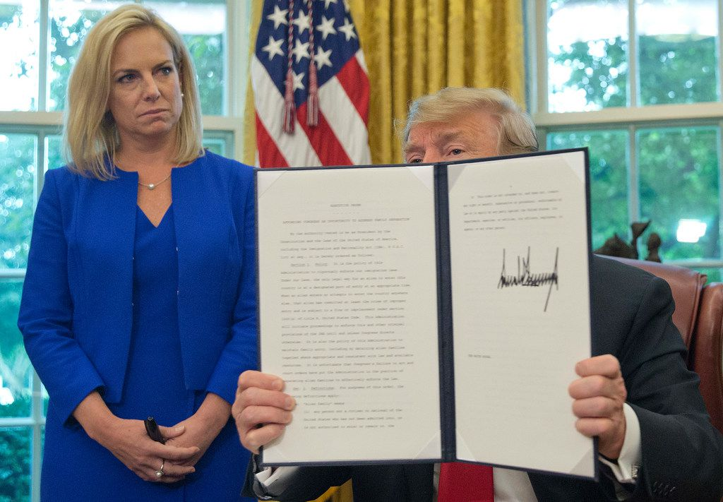 President Donald Trump holds up an executive order he signed on Wednesday. Looking on is Homeland Security Secretary Kirstjen Nielsen, left. (AP Photo/Pablo Martinez Monsivais)