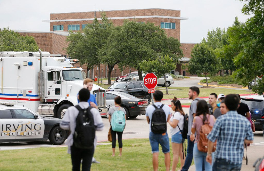 People watch as police investigate after a shooting at North Lake College.