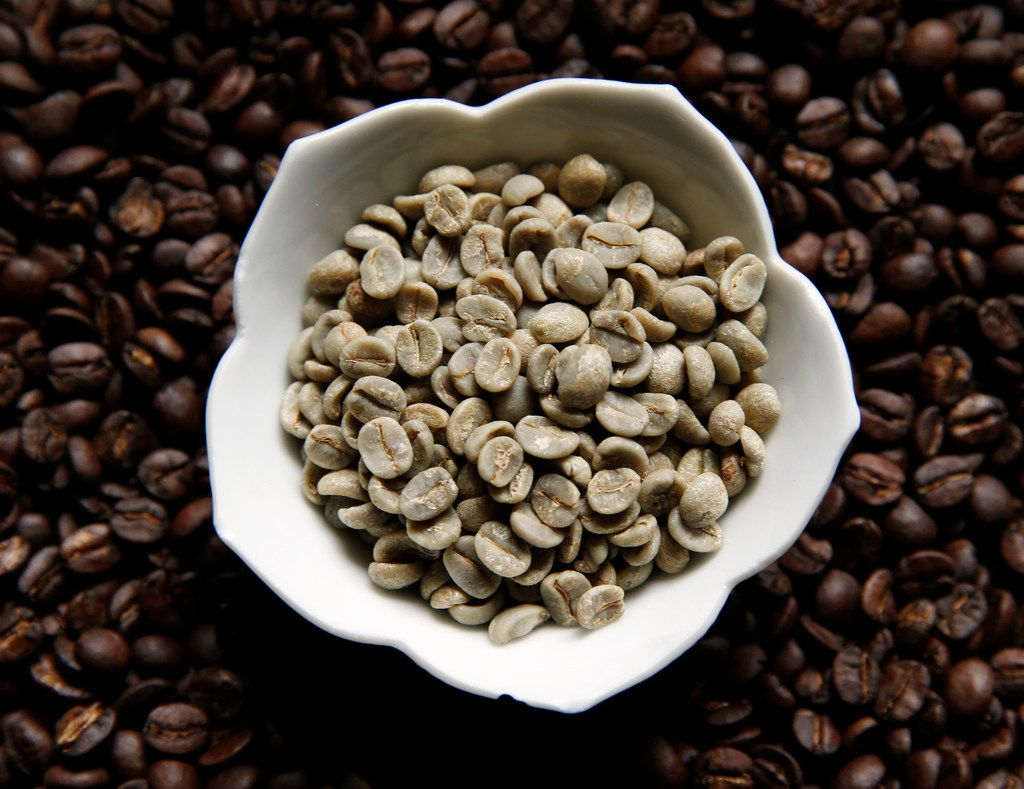 Sweet Maria's Brazil Dry Process Serrinha Yellow Bourbon green coffee beans sit on top of the same type of coffee beans after being roasted at Keith Marton's home in Dallas.