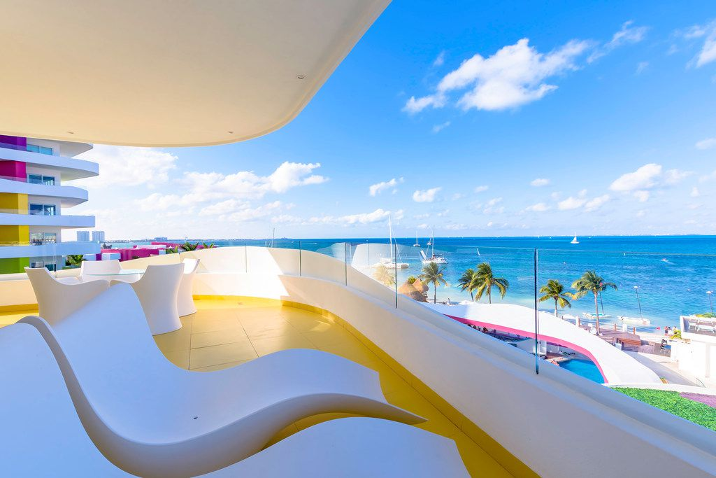 Balconies with sleek, stylish furniture offer views of the Caribbean Sea at Temptation Cancún Resort.
