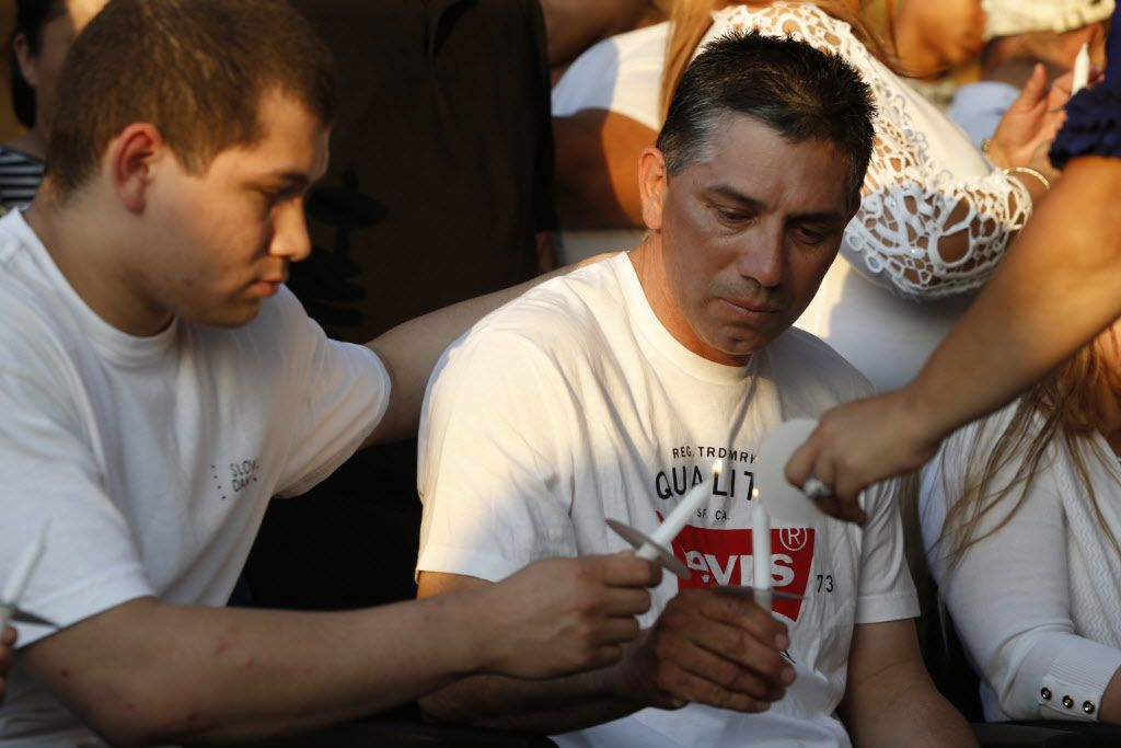 Johnny Gonzalez lights the candle of his father, Juan Gonzalez, during a memorial service held Monday at Irving High School for his daughter Janeera Gonzalez, the North Lake College student slain Wednesday.