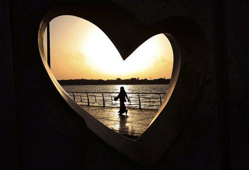 Una mujer vista a través de una estatua con forma de corazón camina por un malecón frente al mar en Yeda, Arabia Saudí, el 11 de mayo de 2011. Una joven causó polémica en Arabia Saudí el julio de 2017 por colocar en internet un video de ella vestida con minifalda y blusa al ombligo, faltando a las estrictas reglas de vestimenta para las saudíes. (AP Foto/Hasan Jamali, Archivo)