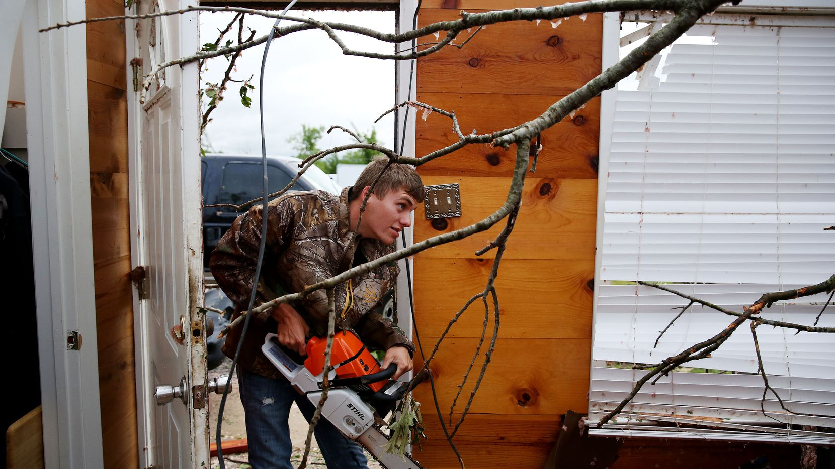Brandon Sherwood prepares to cut down a tree that fell in the living room belonging to his girlfriend family along County Road 1910 after a tornado impacted Fruitvale, Texas on Sunday April 30, 2017.  (Andy Jacobsohn/The Dallas Morning News)