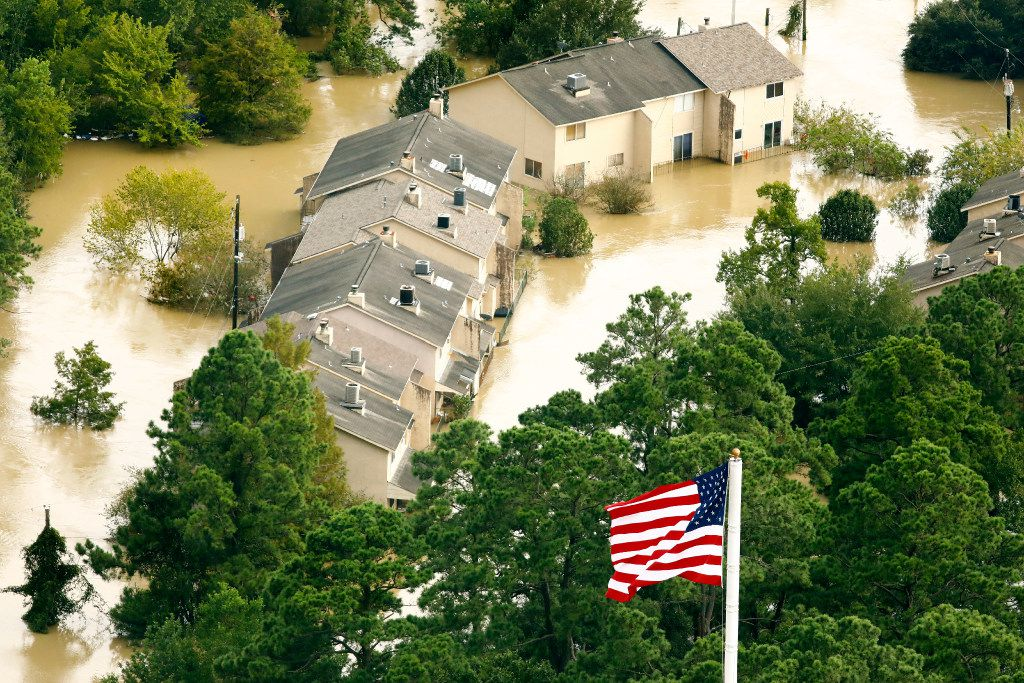 The U.S. flag flies before the River View Townhomes which are surrounded by the overflowing San Jacinto River in Kingwood, Texas, Wednesday, August 30, 2017. Hurricane Harvey inundated the Houston area with several feet of rain.
