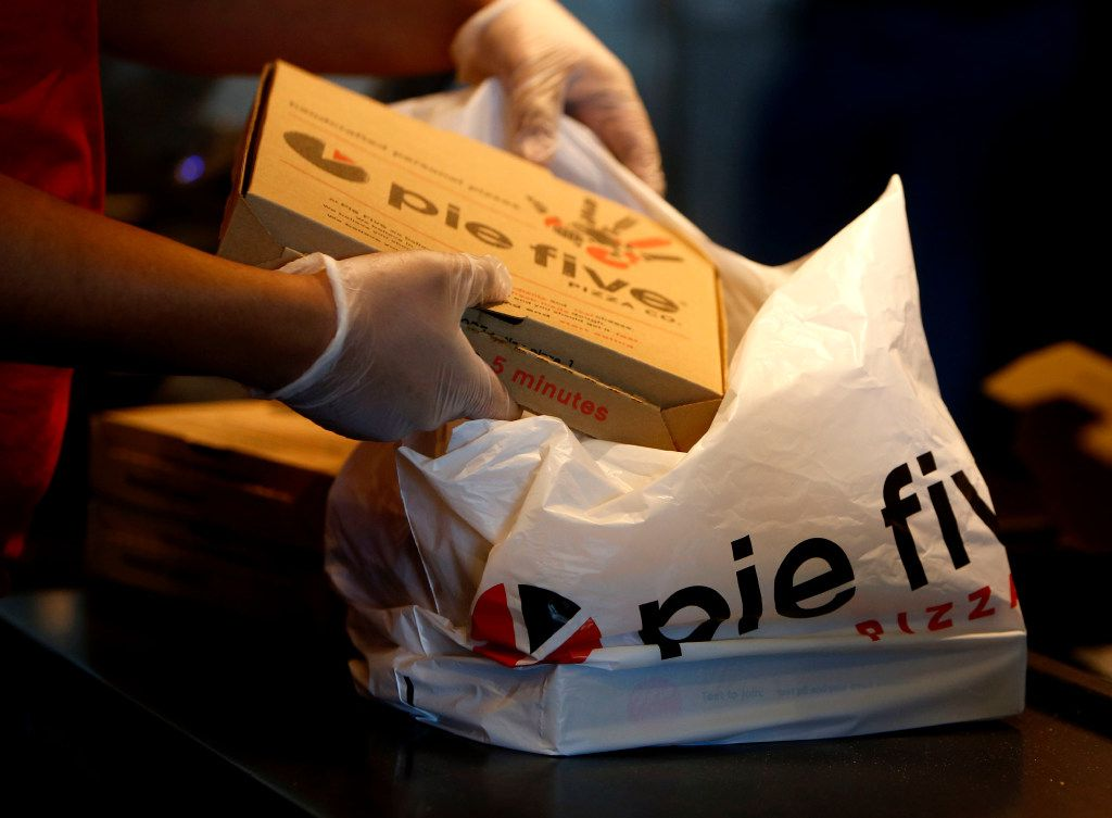 Victor Enriquez puts pizza into a bag at Pie Five in Lewisville, Texas on Friday, Dec. 30, 2016. (Rose Baca/The Dallas Morning News)