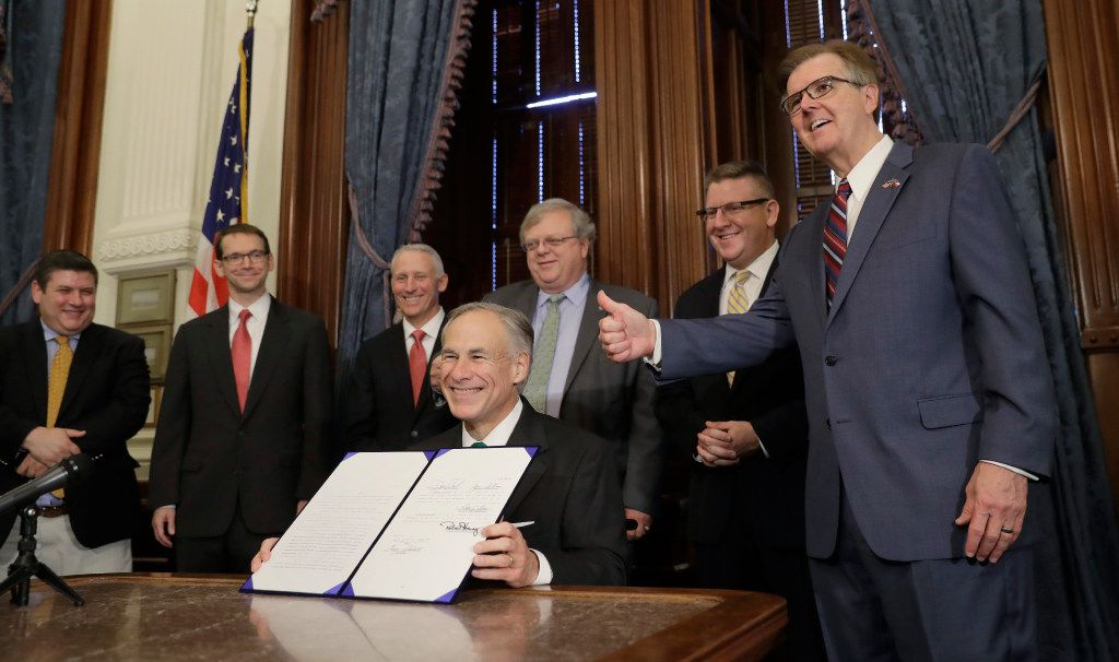 Texas Lt. Gov. Dan Patrick, right, gives a thumbs up sign as Gov. Greg Abbott, center, holds up SB 7, a bill to address inappropriate teacher-student relationships, after he signed it during a ceremony at the Texas Capitol in Austin on May 25, 2017.