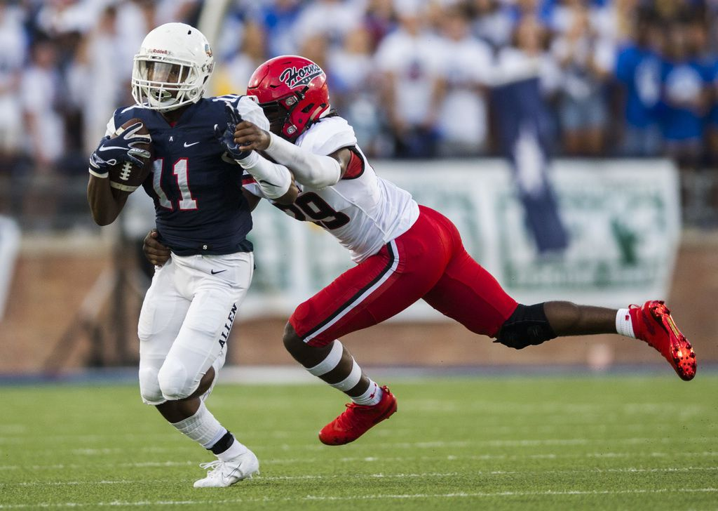 Allen running back Jordan Johnson (11) is tackled by Cedar Hill linebacker Jaheim Lowe (29) during the first quarter of a high school football game between Allen and Cedar Hill on Friday, August 30, 2019 at Eagle Stadium in Allen. (Ashley Landis/The Dallas Morning News)