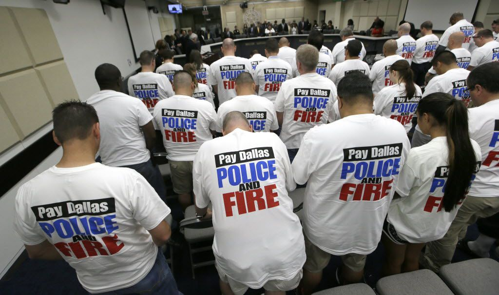 Dallas police and firefighters fill the gallery for a city council budget meeting at Dallas City Hall, Tuesday, Aug. 9, 2016, in Dallas. Dallas police expect to spend $32 million in overtime this fiscal year to fight violent crime, adjust for attrition and pay for extra hours after five officers were slain. (AP Photo/LM Otero)