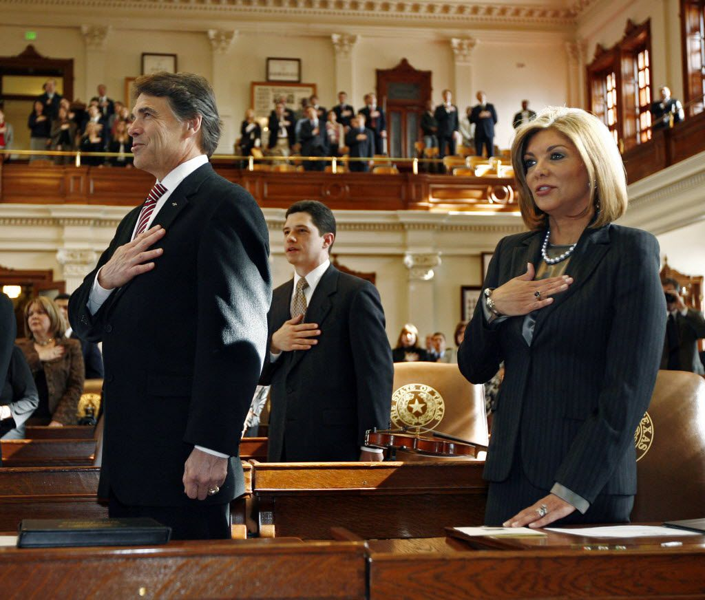 Justice Eva A. Guzman, right, recites the Pledge of Allegiance next to Texas Gov. Rick Perry before being sworn into the Texas Supreme Court in 2010.