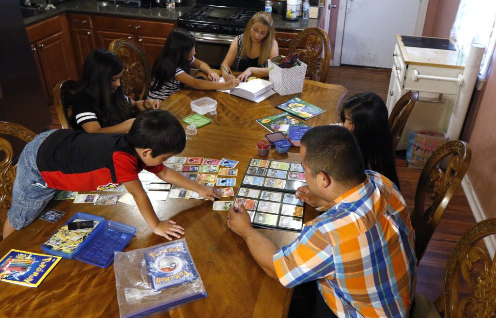 Mauricio Aguilar, 37, right, plays Pokémon with his son, Mauricio, 7, left, as Valerie, 13, Vivian, 9, Cindya, mother, and Vivian, 9,  from left, gather at the family's dining room on Thursday, June 22, 2017 in Dallas. Mauricio upgraded his work skills to provide more for his family.