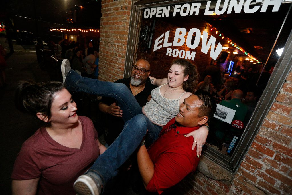 Cambria Battaile (grey) is lifted by Greg Guillard (glasses) and Many Seng with Ashley Null for a photo to be taken during the last hours of operation of the Elbow Room in Dallas on April 16, 2017. (Nathan Hunsinger/The Dallas Morning News)