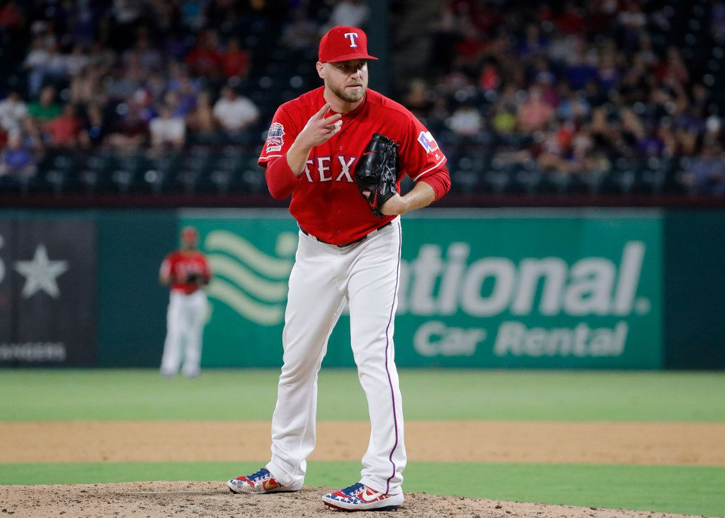 Texas Rangers' Shawn Kelley signals to the plate in the eighth inning of a baseball game a against the Minnesota Twins in Arlington, Texas, Saturday, Aug. 17, 2019. (AP Photo/Tony Gutierrez)