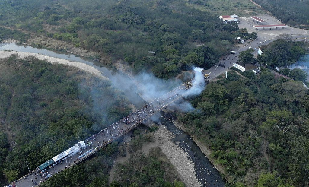 Aerial picture showing demonstrators and smoke billowing from trucks which were carrying humanitarian aid and which were set ablaze on the Francisco de Paula Santander International Brige between Cucuta in Colombia and Urena (R) in Venezuela, on February 23, 2019. - A truck loaded with humanitarian aid was set ablaze on Saturday on the Colombia-Venezuela border, an opposition deputy told reporters amid rioting on the Santander bridge crossing.