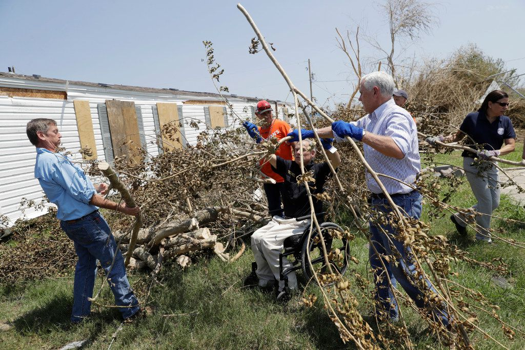 Vice President Mike Pence, center right, and Texas Gov. Greg Abbott, center in wheel chair, help move debris during a visit to an area hit by Hurricane Harvey, Thursday, Aug. 31, 2017, in Rockport, Texas. (AP Photo/Eric Gay)