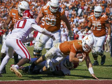 Texas quarterback Sam Ehlinger (11) scores on a 4-yard touchdown run past Oklahoma linebacker DaShaun White (23) during the second half of the Longhorns' 34-27 loss in the Red River Showdown at the Cotton Bowl on Saturday, Oct. 12, 2019, in Dallas.