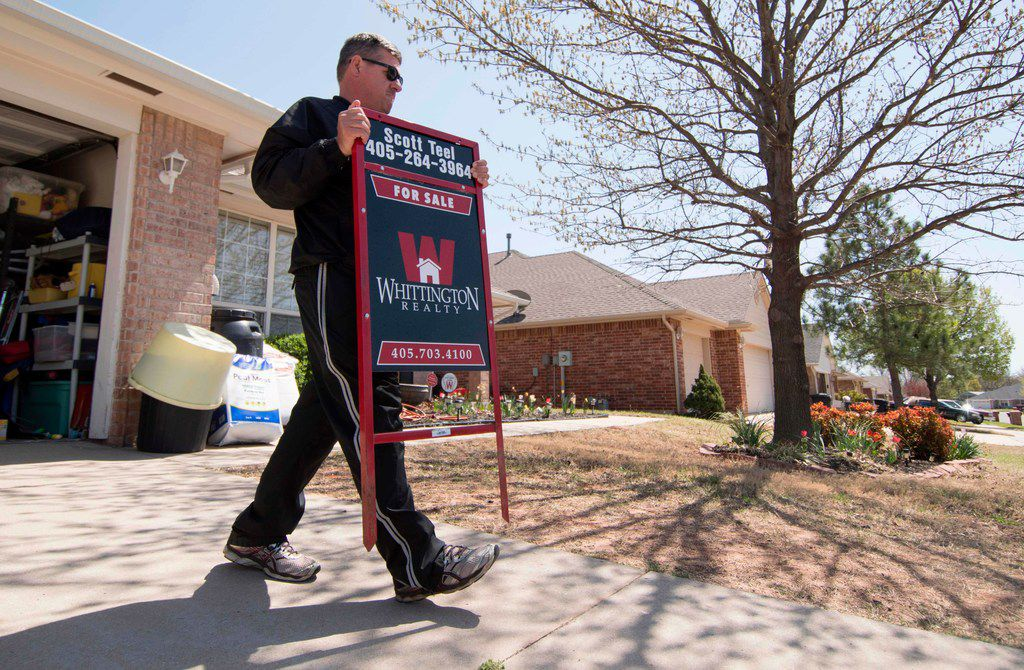 Scott Teel, a high school history teacher in Moore, Okla., carries a 'for sale' sign, as part of his second job as a real estate agent.