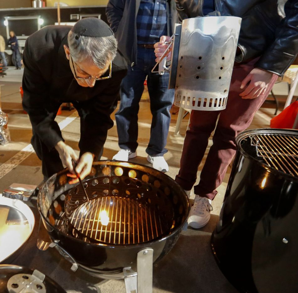 Kosher supervisor or mashgiach, Moe Gabbai, lights the fire in one of the smokers at the Dallas Kosher BBQ Championship on Saturday, Oct. 28. To keep the event kosher, the fire in each team's grill or smoker had to be lit by a rabbi or a kosher supervisor.