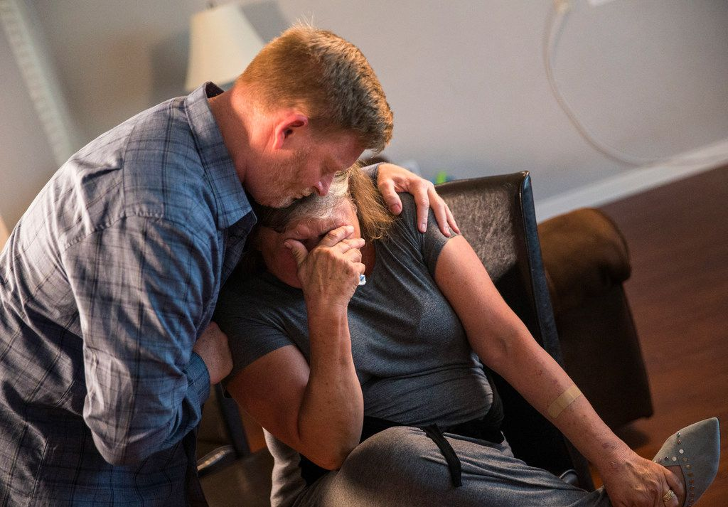 Paul Clyde, left, embraces his ex-wife Nubia Brede Solis during an interview with The Dallas Morning News on Wednesday, June 19, 2019, in Plano, Texas.  Brian Clyde, 22, opened fire on the Earle Cabell Federal Building and was shot by officers and died in a downtown Dallas parking lot.