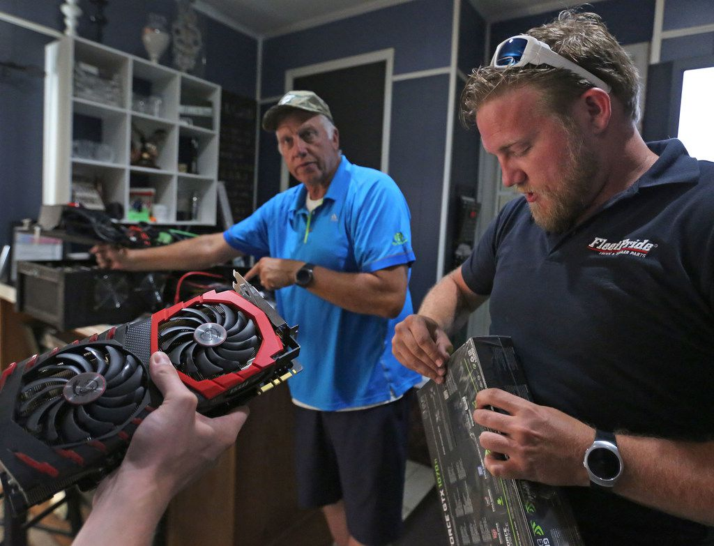 Brandon Edgar, a cryptocurrency enthusiast and technologist who runs a cryptocurrency meet-up in DFW, is pictured with his father Stanley Edgar with their setup at his home in Rockwall, Texas, on Tuesday, May 29, 2018. (Louis DeLuca/The Dallas Morning News)