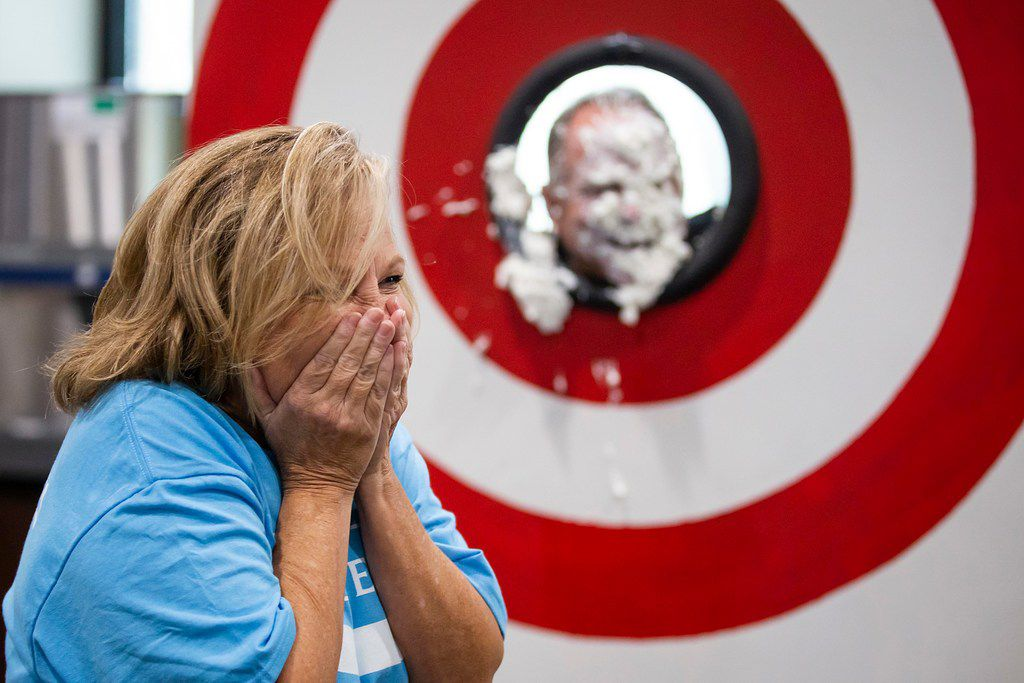 Penny Martin reacts after hitting Joey Hall, executive vice president, Permian operations, with a pie during Pioneer Fair at Pioneer Natural Resources  in Irving.  The pie-in-the-face for executives was the result of reaching fundraising goals for the event, with proceeds benefiting the North Texas Food Bank.