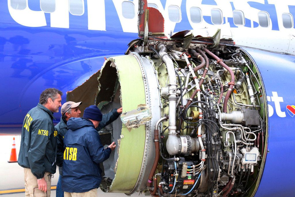 National Transportation Safety Board investigators examine damage to the engine of the Southwest Airlines plane that made an emergency landing at Philadelphia International Airport in Philadelphia on Tuesday, April 17, 2018. (NTSB via AP)