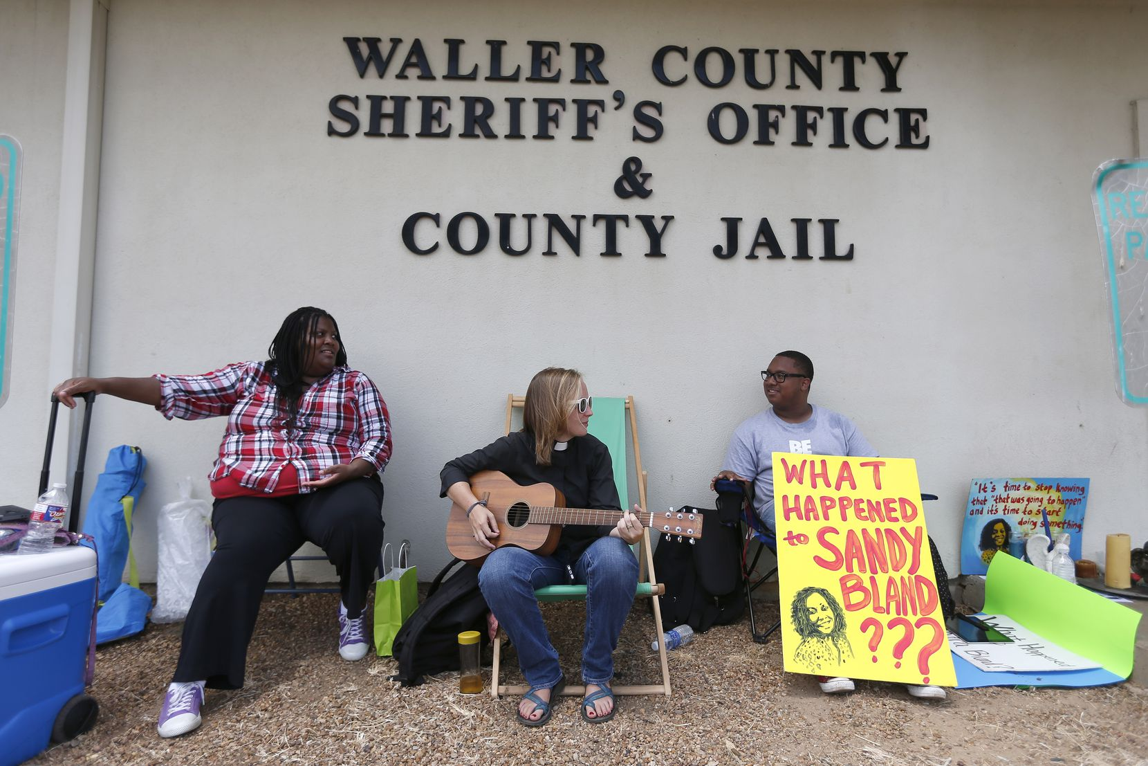 Carie Cauley, left, Rev. Hannah Bonner and Rhys Caraway protest, after the death of Sandra Bland, as they sit in front of the Waller County Sheriff's Office and county jail on Monday, July 20, 2015, in Hempstead, Texas. Authorities said Bland hanged herself in the jail three days after being pulled over by police for a traffic violation and then arrested for allegedly kicking an officer during the stop. Bland's family is ordering an independent autopsy, lawyers said. (Karen Warren/Houston Chronicle via AP) MANDATORY CREDIT