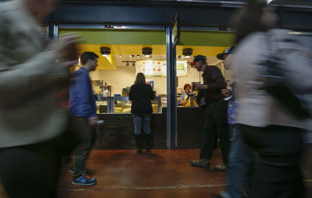 """Attendees at The Market's soft opening past the """"doc popcorn"""" store at Dallas Farmers Market Friday December 11, 2015.  (Ron Baselice/The Dallas Morning News)   [ This is located in the building formerly called Shed 2 at the Dallas Farmers Market ]"""