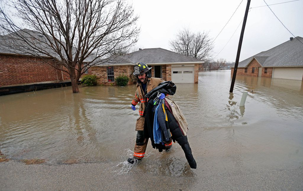 A Rockwall firefighter carries clothing out of the flooded house on Lakeside Drive in Rockwall, Texas, Thursday, Feb. 22, 2018.