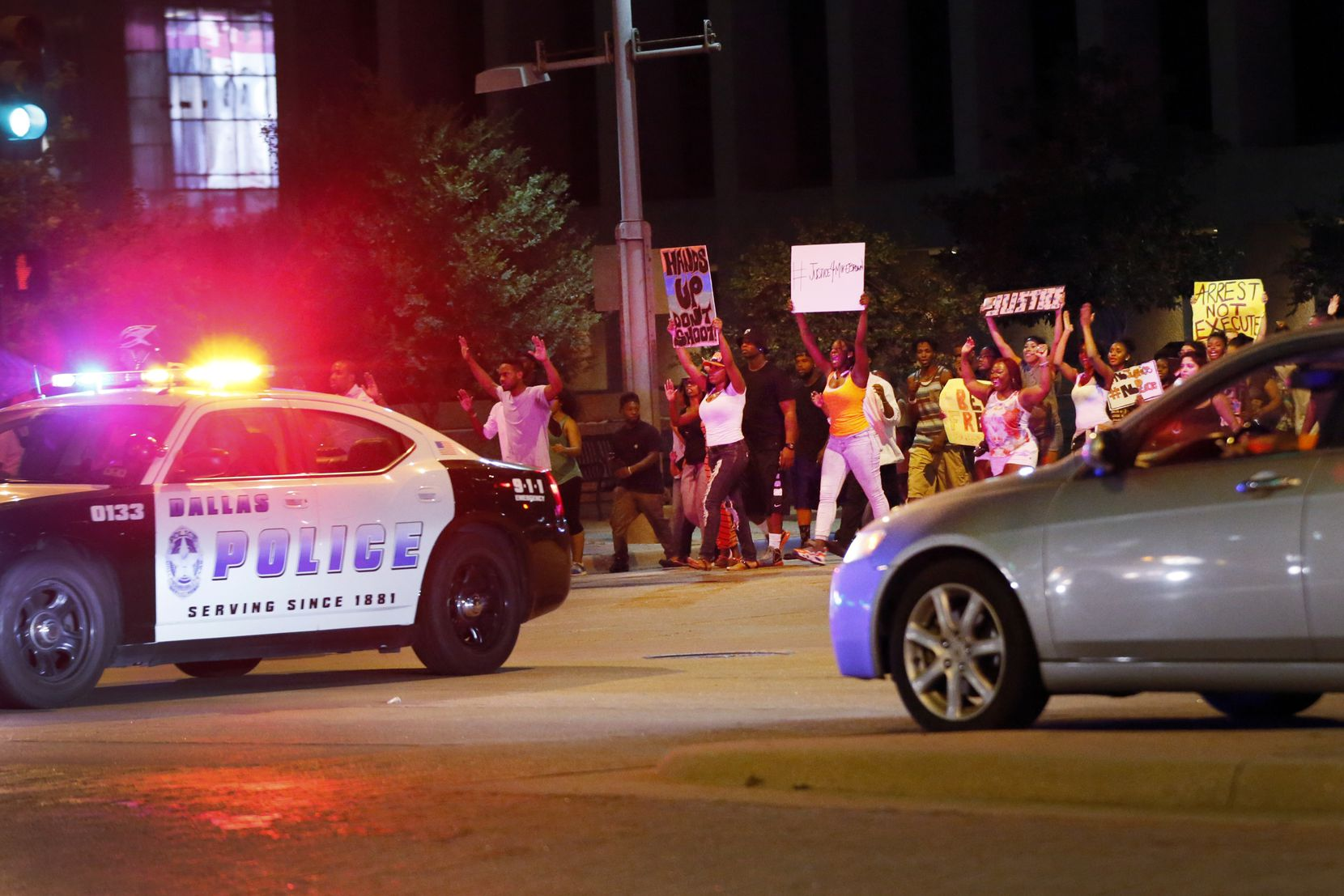 People walk along Mainr Street in Downtown Dallas near South Griffin Street while they participate in a hands up rally in support of gunned down Ferguson Missouri teen Mike Brown August 20, 2014. (Kye R. Lee/The Dallas Morning News)