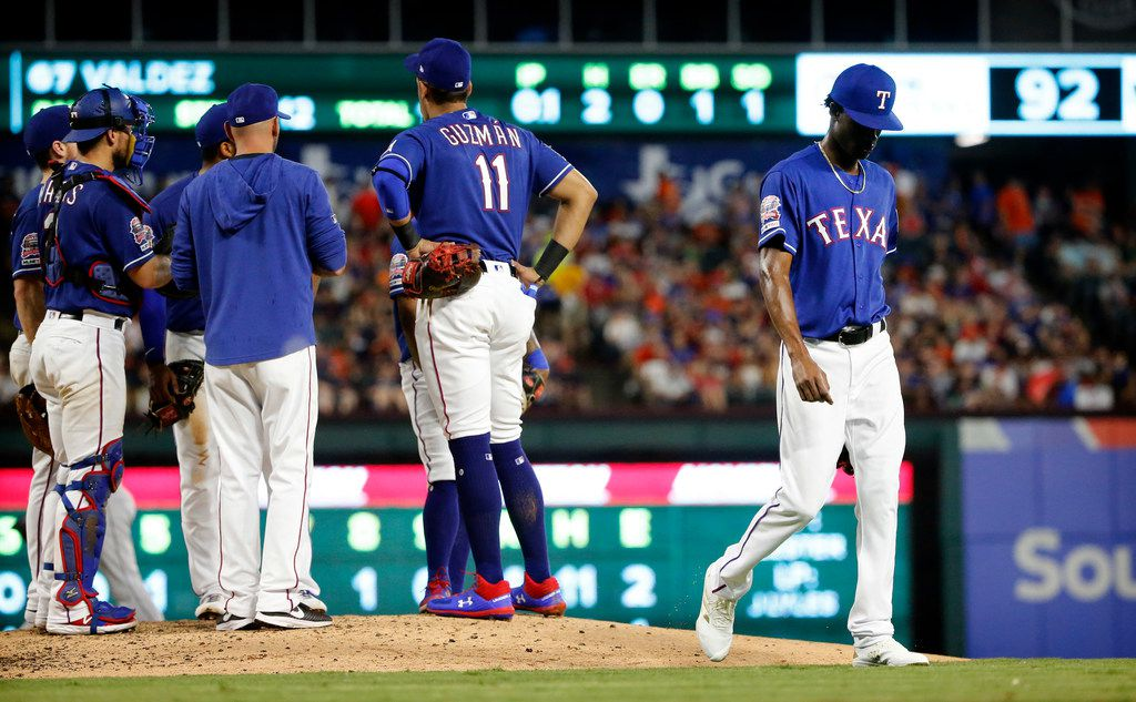 Texas Rangers relief pitcher Phillips Valdez (right) walks to the dugout after being pulled by manager Chris Woodward (8) in the sixth inning against the Houston Astros at Globe Life Park in Arlington, Texas, Saturday, July 13, 2019.  (Tom Fox/The Dallas Morning News)