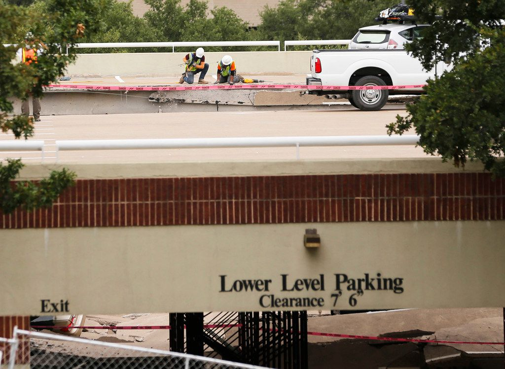 Workers removed debris off of the upper level of a parking garage off of O'Connor Ridge Boulevard in Irving on Wednesday.