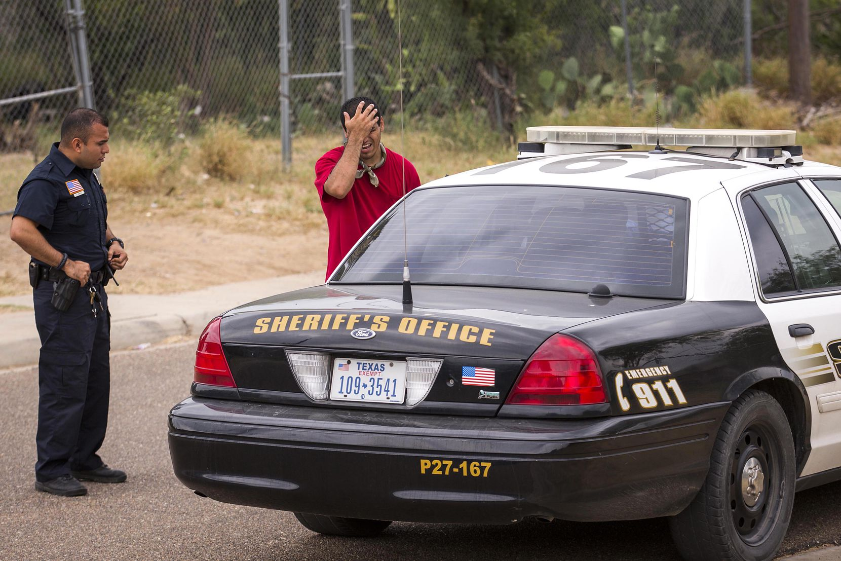 El Cenizo Police Chief Edgar Garcia (left) joins a Webb County Sheriff's deputy as they ask a local resident if he a has seen someone described in a 911 call about a suspicious person on, May 11, 2017, in El Cenizo, Texas.