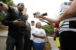 Dominique Alexander (from left), Rev. Ronald Wright, Damon Crenshaw and LaShaun Steward talk to the media about Steward's sister, D'Lisa Kelley, a 24-year-old pregnant woman who was found beaten and strangled after disappearing on the way to a friend's wake, expressing their frustration that there have been no leads in the case outside the DPD headquarters in Dallas on Tuesday, June 10, 2014. (Lara Solt/The Dallas Morning News)