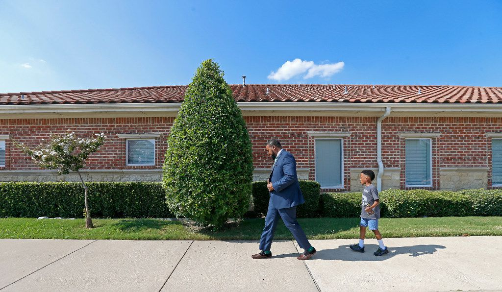 Attorney Lee Merritt (left) and his 7-year-old son Stacy Merritt, Jr., walks to the North Texas Orthodontic Associates' office in Allen.