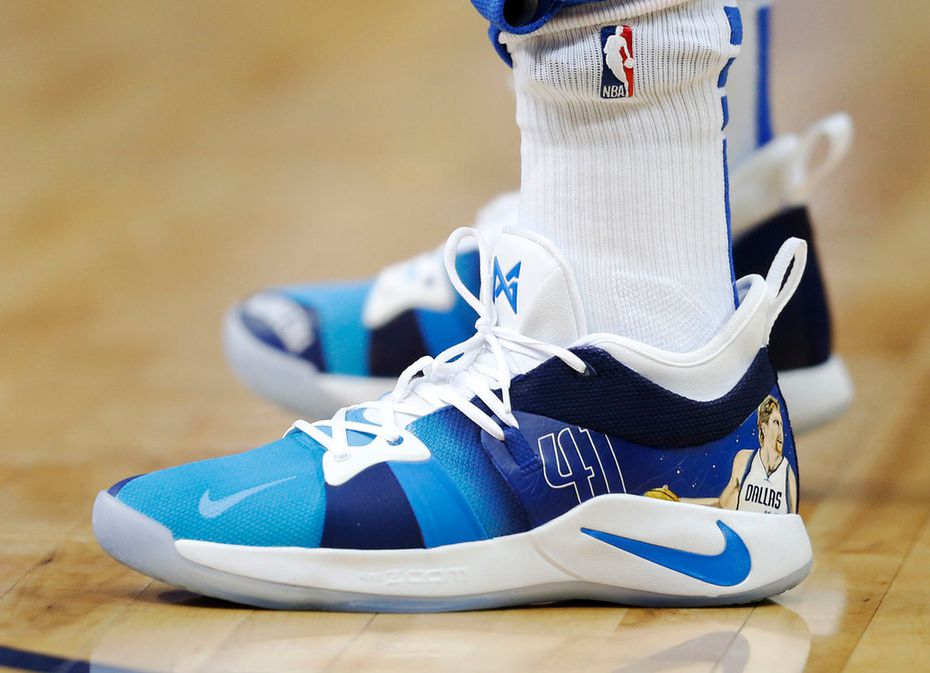 Mavericks guard/forward Luka Doncic (77) sports some custom Nike shoes with Dirk Nowitzki (41) on them during warmups in a game against the Phoenix Suns at American Airlines Center in Dallas on Tuesday, April 9, 2019. (Vernon Bryant/The Dallas Morning News)