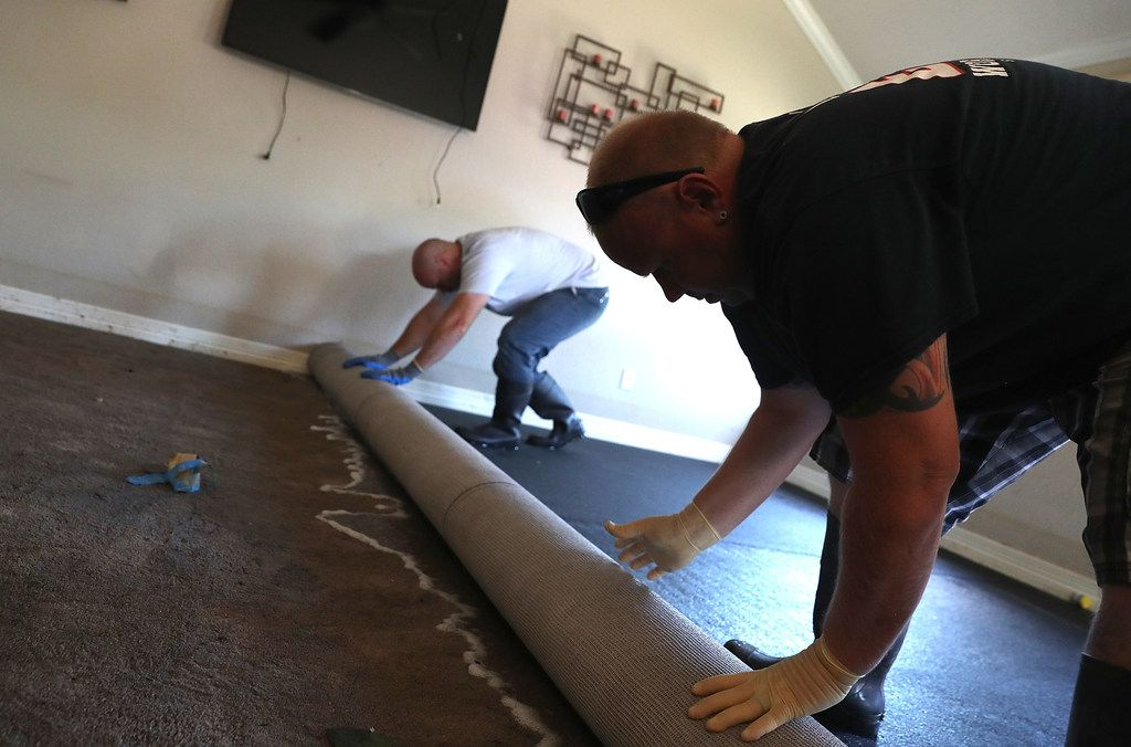 RICHWOOD, TX - SEPTEMBER 07: Mike Praslicka (R) rolls up a wet carpet with Justin Davison (L) in his flood damaged home on September 7, 2017 in Richwood, Texas. Over a week after Hurricane Harvey hit Southern Texas, residents are beginning the long process of recovering from the storm.  (Photo by Justin Sullivan/Getty Images)