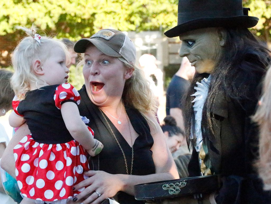 Tiffany Quast (center) of Plano shows a Trunk or Treat maniquan to her daughter Sadie, 2, as St. Andrew United Methodist Church held its annual community fall festival on Sunday, October 28. (Stewart F. House/Special Contributor)