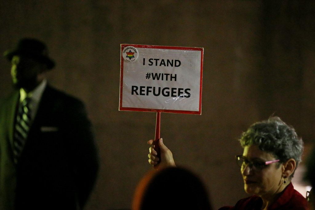 """Linda Evans holds up a sign that reads """"I STAND #WITH REFUGEES"""" during a protest among refugee advocates in Thanks-Giving Square in downtown Dallas on Nov. 13, 2017."""