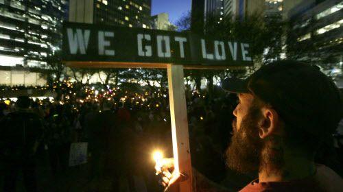 """Paul Milano sostiene un cartel que dice """"Nosotros damos amor"""" durante la vigilia del lunes en Thanks-Giving Square en Dallas. LM OTERO/AP"""