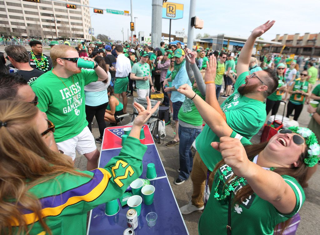 "A spirited ""Flip Cup"" competition is held along the parade route during the Dallas St. Patrick's Parade & Festival along Greenville Avenue in Dallas on Saturday."