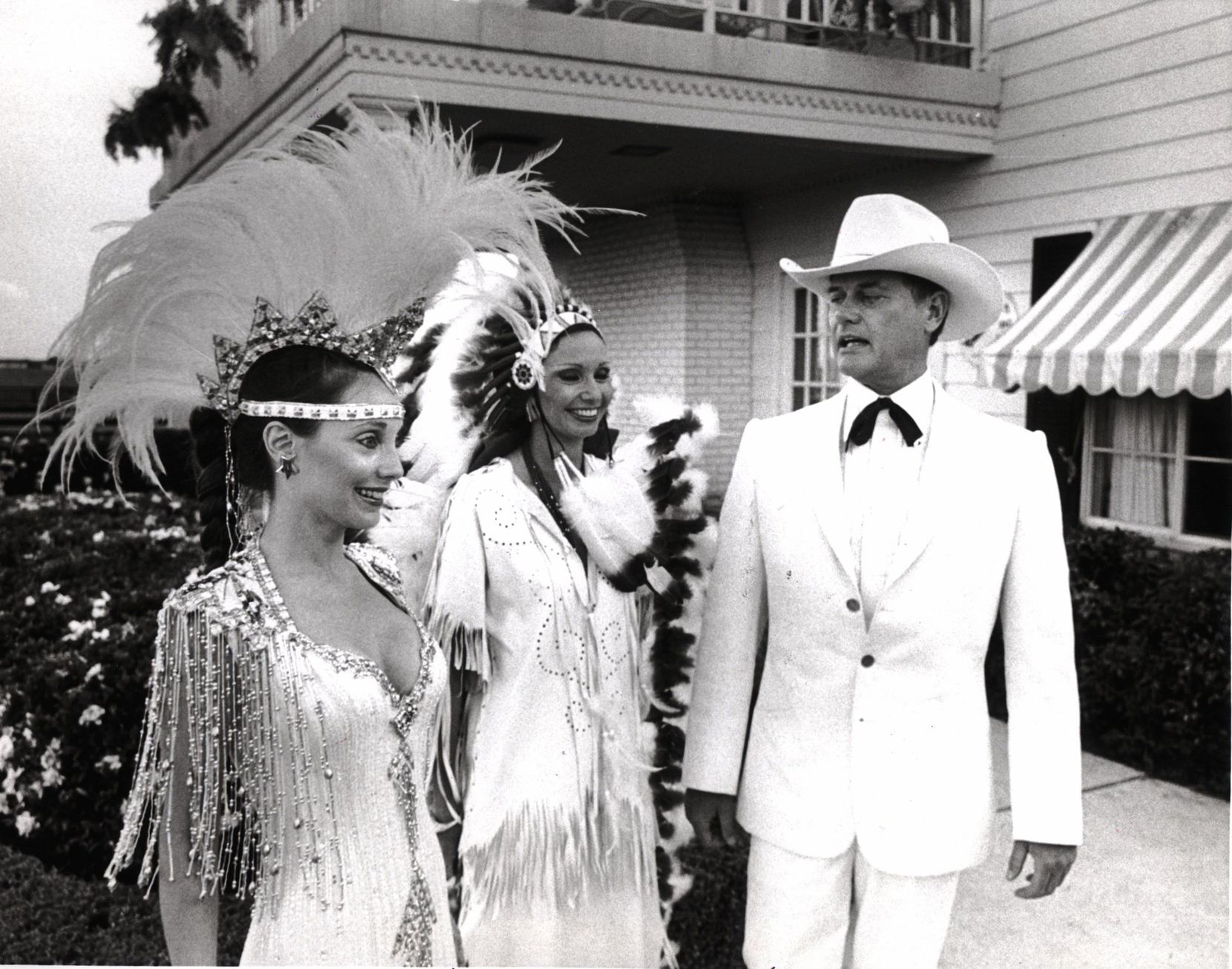 Larry Hagman wore his white, doe-skin tuxedo to the 1981 Cattle Baron's Ball where he posed with co-chairs  Melinda Wynn and Frances Sheperd. Later in the evening, he was covered in mud.