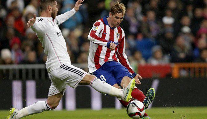 Sergio Ramos (izq.) y Fernando Torres disputan el balón en el juego de octavos de final de la Copa del Rey el jueves en el estadio Bernabéu. (AP/DANIEL OCHOA DE OLZA)