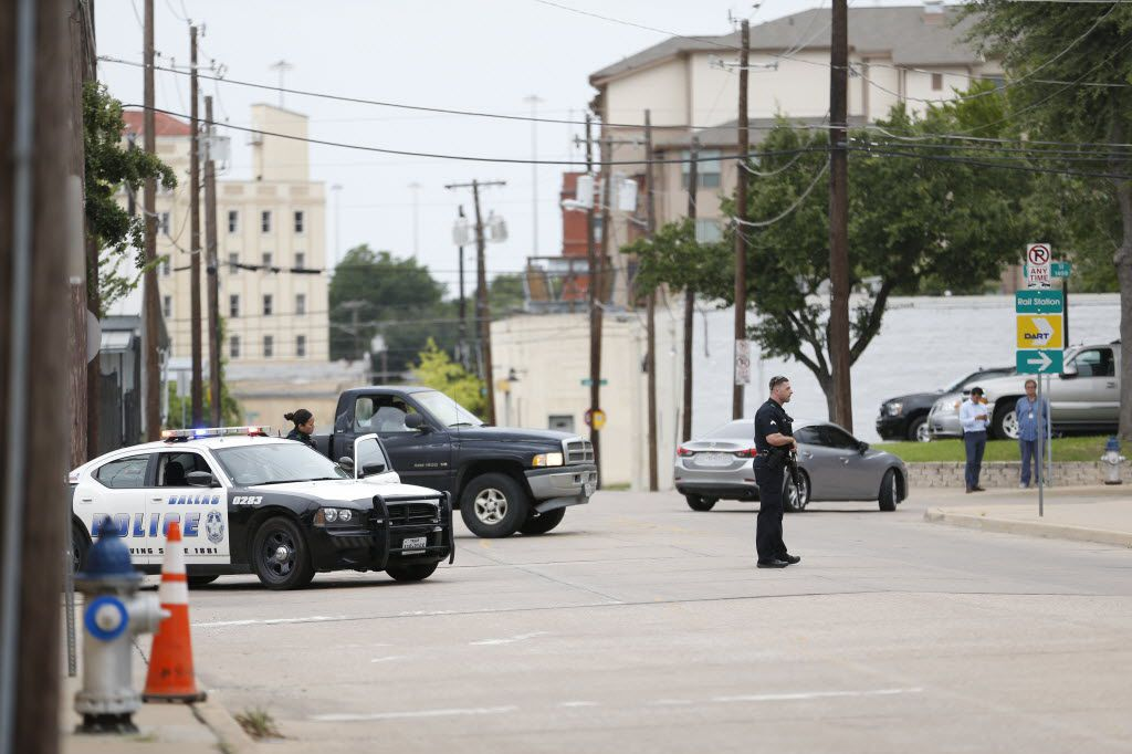 Dallas Police stand guard along Belleview Street near Dallas Police Headquarters in Dallas on July 9, 2016. (Rose Baca/The Dallas Morning News)