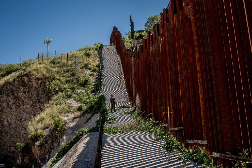 A U.S. Border Patrol agent watches from the U.S. side of the border fence with Mexico in Nogales, Ariz., Sept. 22, 2016. (Tomas Munita/The New York Times)